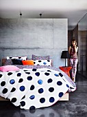 Bed linen with blue polka dots on double bed against concrete partition wall in minimalist sleeping area