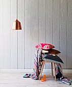 Stack of cushions on wooden chair and pendant lamp with copper lampshade in front of wooden wall