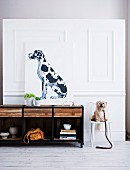 Portrait of dog on top of sideboard and small, white dog sitting on chair against white, wood-panelled wall