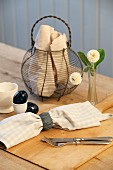 Breakfast in rustic ambiance - linen napkin and cutlery in front of wire basket on wooden table