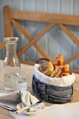 Breakfast rolls in bread basket upcycled from jeans on table in rustic ambiance