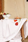 Tablecloth embroidered with floral motif on wooden table