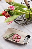Mobile phone in hand-embroidered pouch next to wire basket of spring flowers