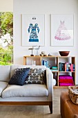 Comfortable designer sofa with scatter cushions, framed fashion illustrations and wooden shelves against wall in background
