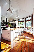 Light-flooded kitchen with wooden floor & retro pendant lamps hanging from white wooden ceiling above island counter