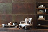 Hand-crafted armchair upcycled from wooden pallets with pale cushions between TV cabinet and shelving against corten steel wall