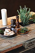 Potted herbs and candle on rustic dining table made from pallet