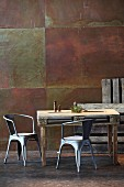Rustic dining table made from pallet and metal chairs against corten steel wall