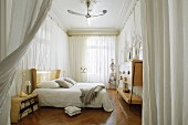 Long bedroom with pale wooden furniture against walls covered in circumferential curtains