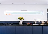 Long, designer kitchen counter with blue base units against wall with narrow ribbon window
