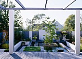 Terrace with pergola in front of modern, landscaped garden with pool