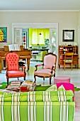 Komplementäre Rot- und Grüntöne - Rokokosessel mit neuen Polsterstoffen, gestreiftem Sofa und Vorhang im Hintergrund