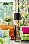 Zeitgenössisches Gemälde auf Biedermeierkommode, gestreifte Polstermöbel und kräftig bunter Vorhang in Rot- und Grüntönen