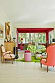 View from seating area with Rococo armchairs, pink stools and modern, striped sofa into dining area in conservatory extension