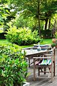 Regiestühle mit bunten Streifen und Tisch auf Holzterrasse im Garten