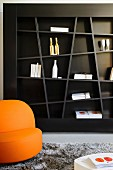 Abstract shelving on dark brown wall and orange armchair in living room