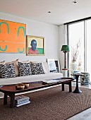 Rustic wooden coffee table on sisal rug in front of pale couch with zebra-patterned scatter cushions and artworks on wall