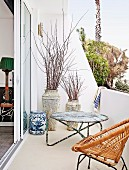 Delicate wicker chair and vintage, metal side table on balcony near beach