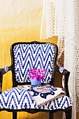 Postmodern chair with white and blue upholstery and black wooden frame against yellow wall draped in lace fabric