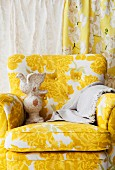 Armchair with yellow and white floral cover and vintage sculpture of bird