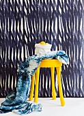 Hand-dyed cloth and yellow-painted stool against blue and white striped wall