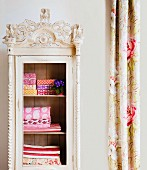 Colourful, patterned, folded fabrics in antique, vintage-style wardrobe