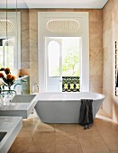 Free-standing bathtub in front of open balcony door and mirrored cabinet doors above sinks in elegant, marble bathroom