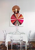 Copper pendant lamp above festively set table with Ghost chairs and picture of colour wheel on wall