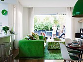 Green accents in open-plan living area with view of young family on terrace