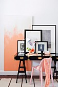 Pastel pink scarf on chair of same colour in front of black-framed pictures on black-painted writing desk