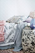 Detail of a boudoir - Side table painted with flowers and birds next to bed with bedspreads and throws