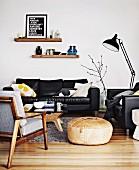 Pouf zwischen Sessel im Fiftiesstil und Ledersofagarnitur, dazwischen schwarze Metall Stehleuchte im Wohnzimmer