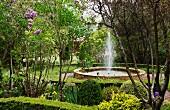 Fountain in round basin in landscaped gardens