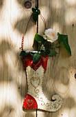 Metallstiefel mit Rose an einer Tür hängend
