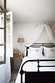Double bed with black metal frame and canopy of white, airy fabric in country-style interior