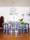 Dining table, classic lamp and brightly coloured bentwood chairs on glossy parquet floor; original 20s' double glass doors in background