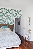 Double bed with wicker headboard against floral wallpaper