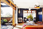 Blue-painted interior with coffee table, partially visible sofa & open sliding door leading to terrace