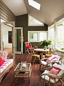 Veranda of wooden house; rattan chairs with scatter cushions and upholstery around coffee table with dining area in background