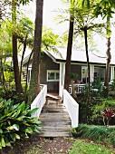 Steg über Bach mit weisssem Holzgeländer vor Wochenendhaus in tropischer Umgebung