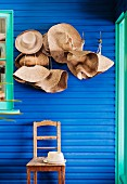 Straw hats on coat pegs and chair against blue wall with turquoise window frame