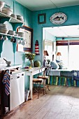 Vintage kitchen painted turquoise with daybed in window niche and maritime decorations on wall