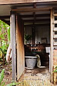 Outdoor bathroom with zinc bathtub in wooden structure with corrugated metal cladding and pebble mosaic floor