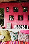 Masonry sofa with scatter cushions in front of pink external wall with ornaments in niches and car registration plate
