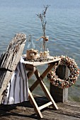 Bottle decorated with shells and jute rope braid on folding table and wreath of shells on wooden jetty next to lake