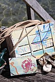 Old fruit crates painted with summery, maritime motifs in acrylic paint on wooden jetty on lake shore