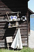 Blue and white crockery on DIY suspended shelves made from wooden boards and jute rope on outside wall of boathouse