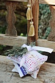 Scented sachets hand-sewn from napkins, tablecloths and doilies and tied together with sprigs of lavender on wooden bench