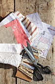 Fabric remnants, trim, sewing scissors and sketches of hand-sewn bag on sunny wooden bench