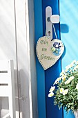 Hand-crafted, heart-shaped felt sign with embroidered message hanging from doorknob